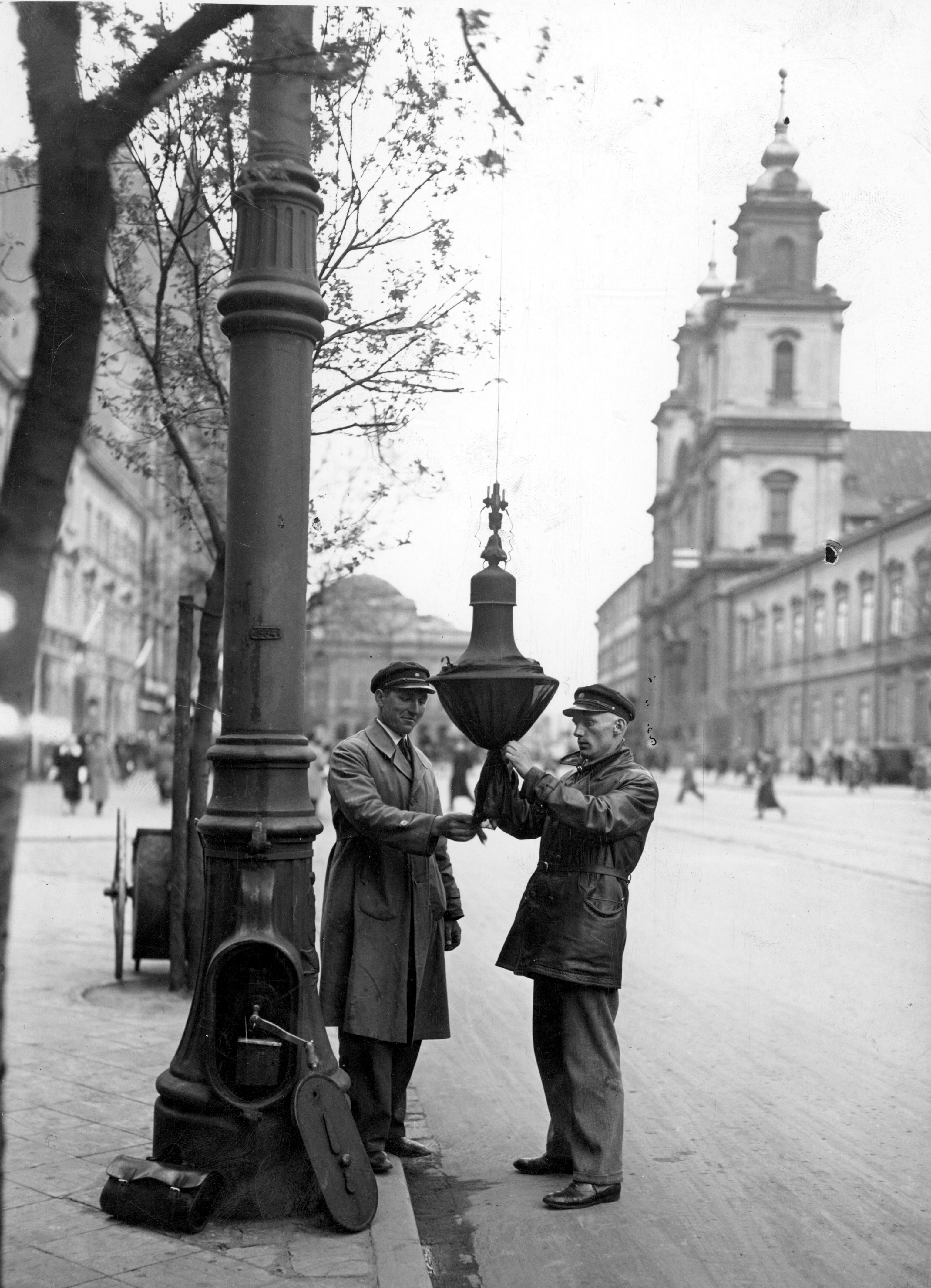 Dwóch mężczyzn zawiesza dekoracje żałobne na latarniach przy Krakowskim Przedmieściu.