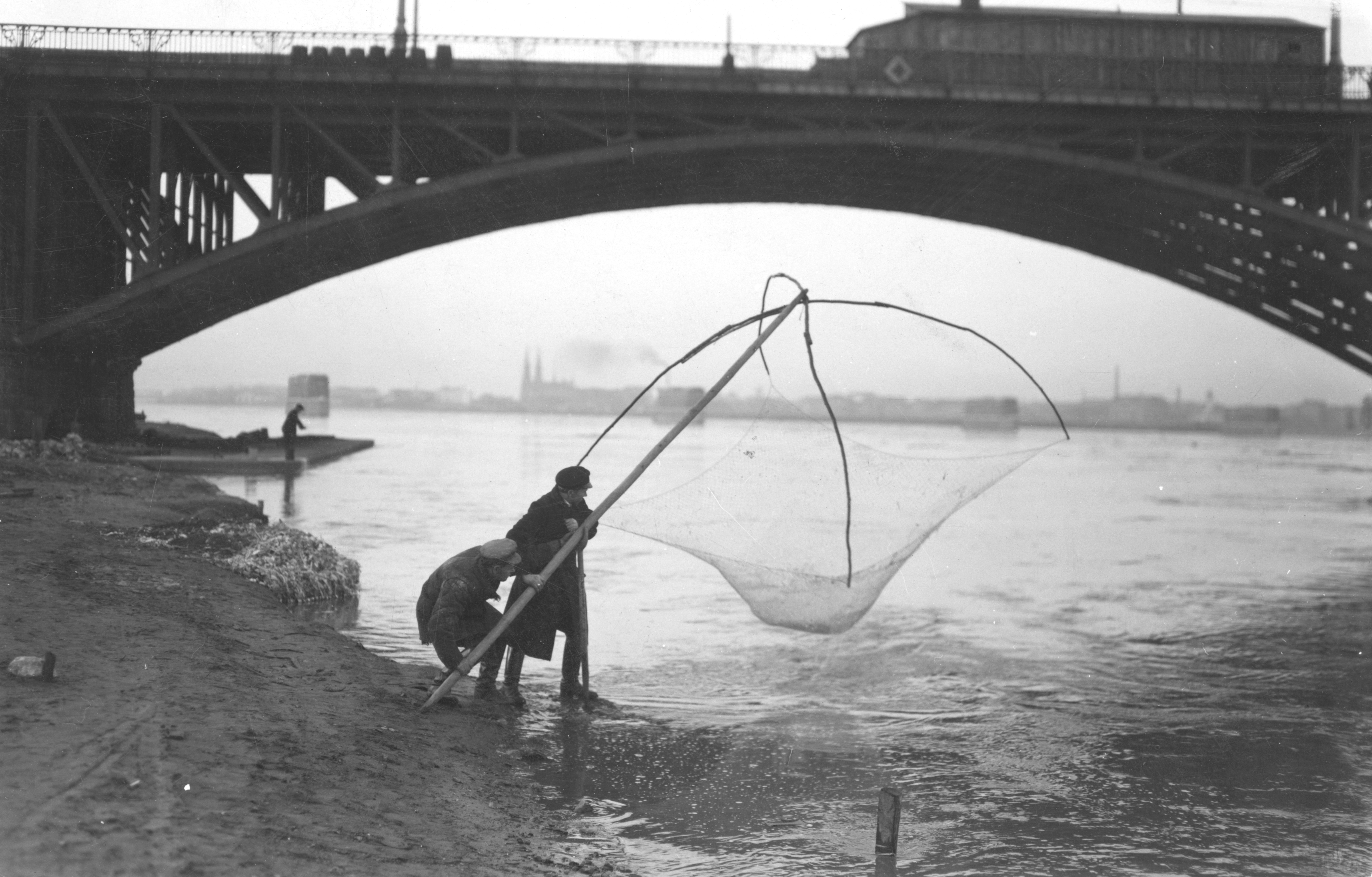 Dwóch mężczyzn stoi z podrywką na brzegu Wisły w Warszawie. Widoczny fragment przęsła mostu Poniatowskiego oraz fragment praskiego brzegu Wisły.