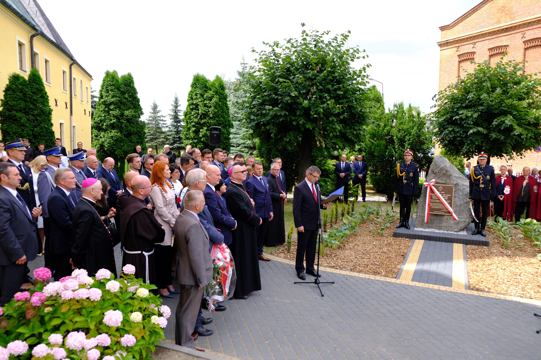 zdjęcie z odsłonięcia pamiątkowej tablicy, po lewej stronie grupa ludzi, przed nimi przemawiający Marszałek Kuchciński, obok tablica pamiątkowa przewiązana biało-czerwoną wstęgą