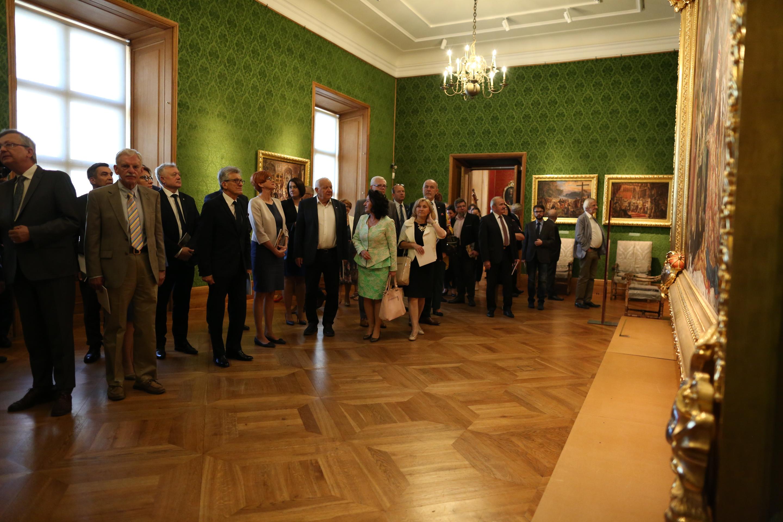 zdjęcie sali wystawowej z cennymi obrazami na ścianach, po środku grupa zwiedzających