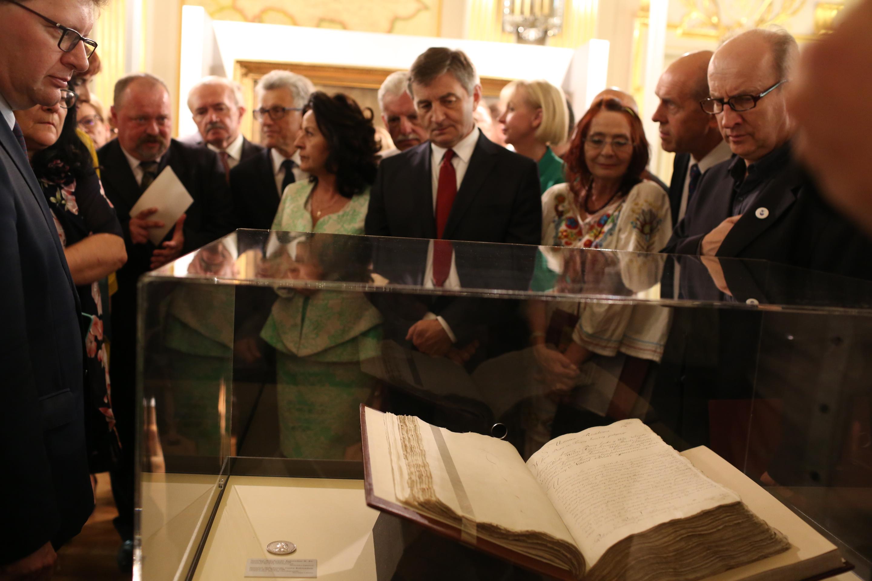 zdjęcie sali wystawowej i gabloty ze starą księgą, której przygląda się wielu widzów