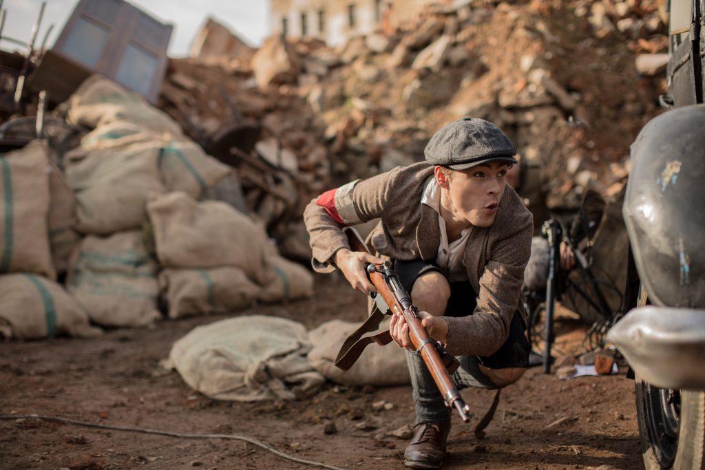 kadr z filmu, przedstawiający powstańca z bronią