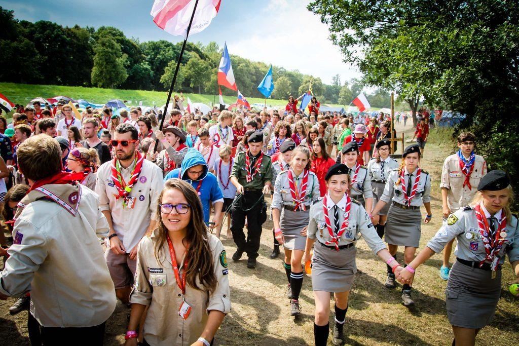 grupa harcerzy maszeruje ścieżką, nad nimi kolorowe flagi wielonarodowe
