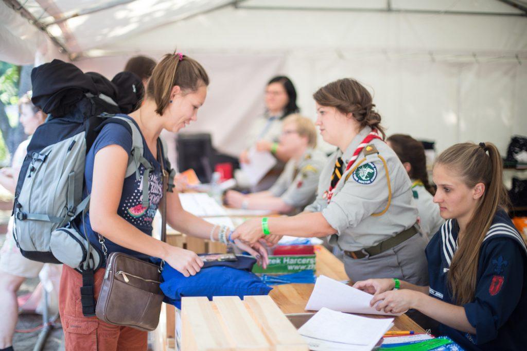 rejestracja przy biurku - dziewczyna z plecakiem ma zakładaną na rękę przez harcerkę opaskę