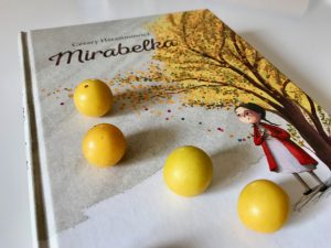 "książka ""Mirabelka"", na której leżą mirabelki"