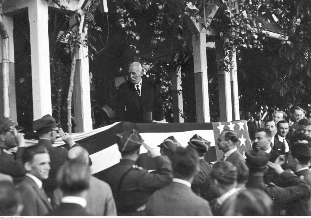 prezydent stoi na trybunie ozdobionej flagą amerykańską