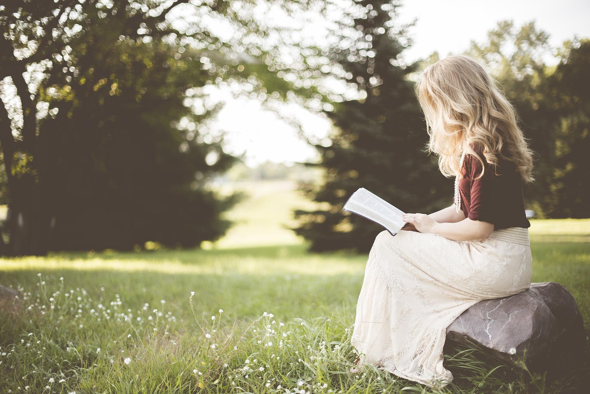 kobieta czytająca na łące książkę