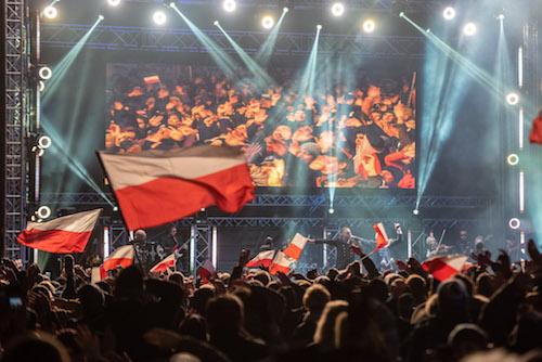 zdjęcie tłumu na koncercie i powiewającej polskiej flagi