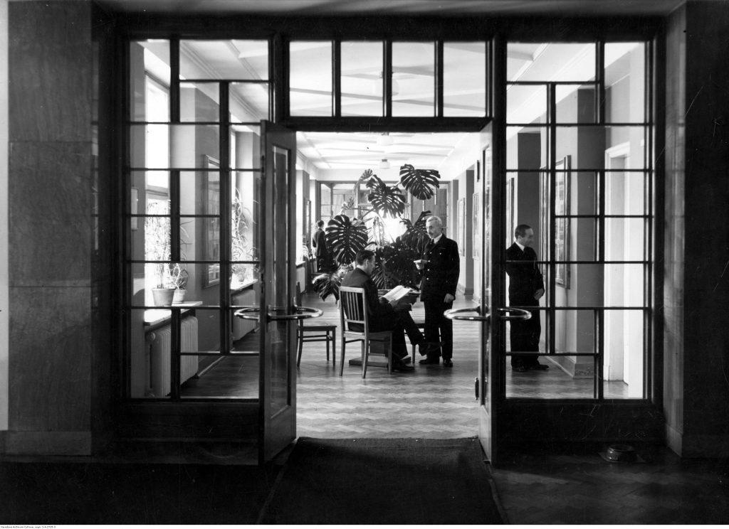 Korytarz ministerstwa, eleganckiego wystroju dopełnia dyskretnie umieszczona przy drzwiach spluwaczka, Narodowe Archiwum Cyfrowe