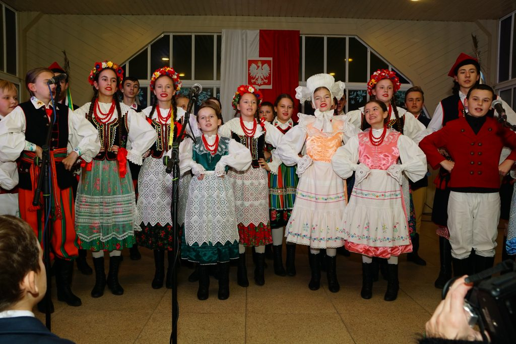 dzieci w strojach regionalnych śpiewają na scenie