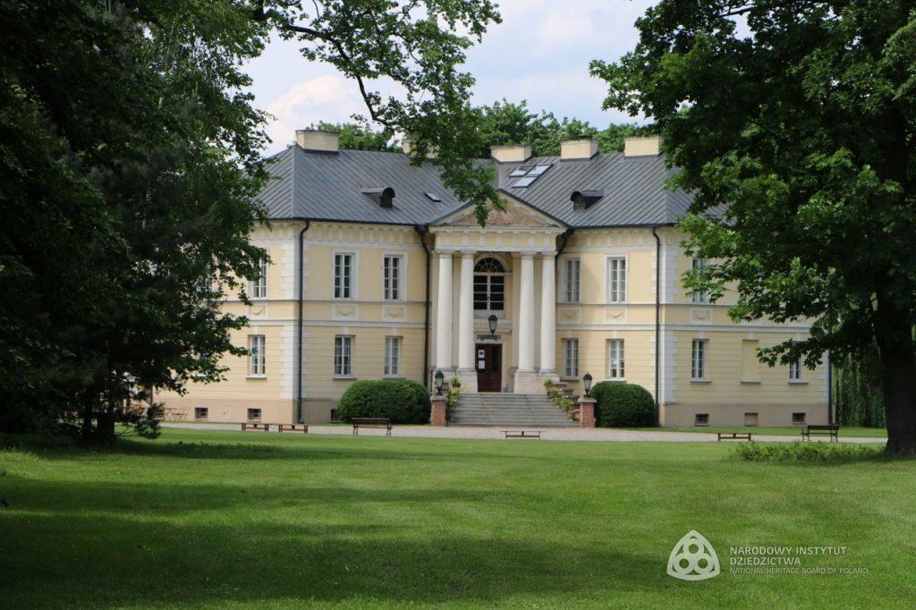 widok na pałac zza drzew liściastych