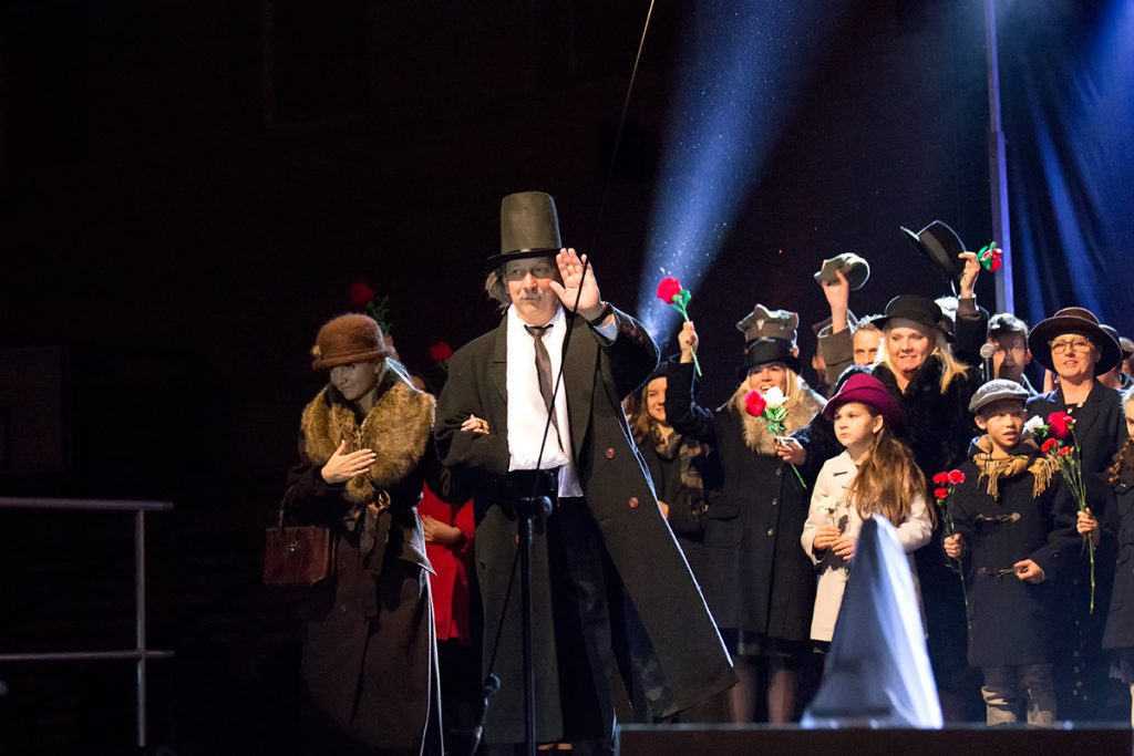 na zdjęciu aktor w przebraniu Paderewskiego z żoną wchodzą na scenę wśród wwatującego tłumu z kwiatami
