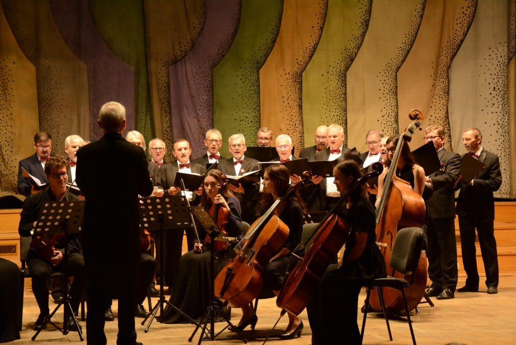 na scenie z przodu orkiestra z instrumentów smuczkowych, w tle śpiewający męski chór
