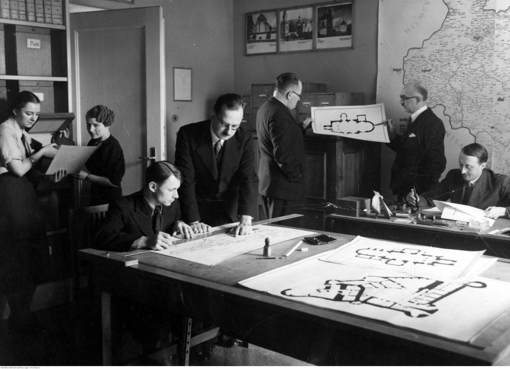 ludzie w biurze, rozłożone plany budynków