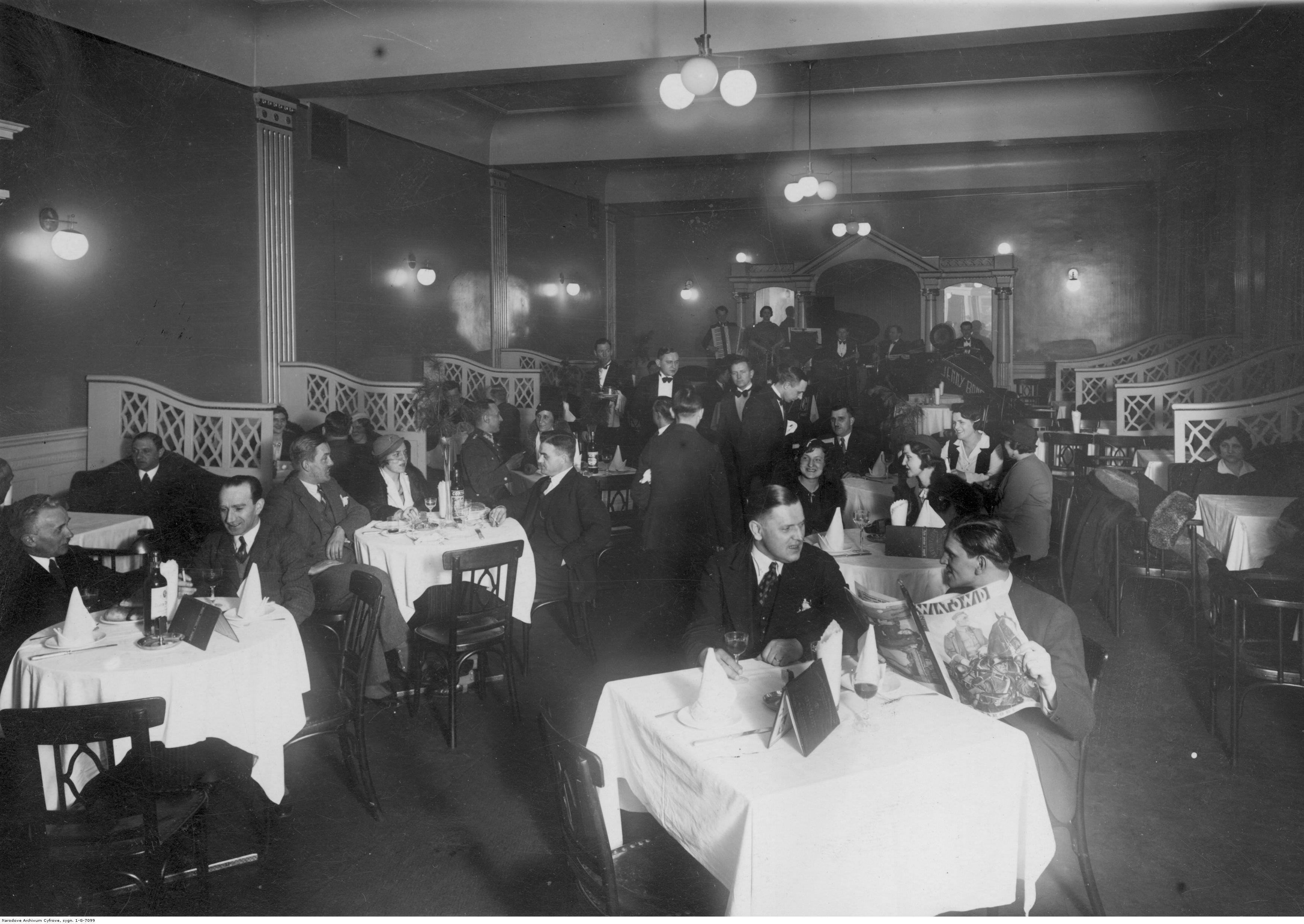 Goście siedzący przy kawiarnianych stolikach.