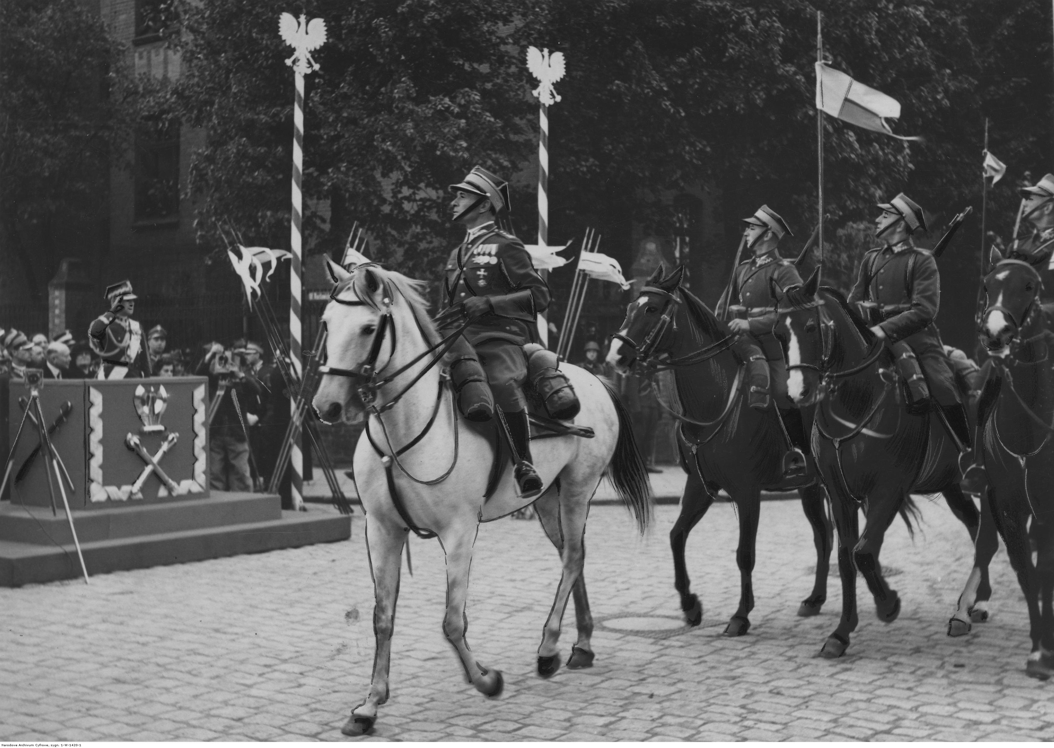 grupa żołnierzy na koniach defiluje przed trybuną na której stoi marszałek