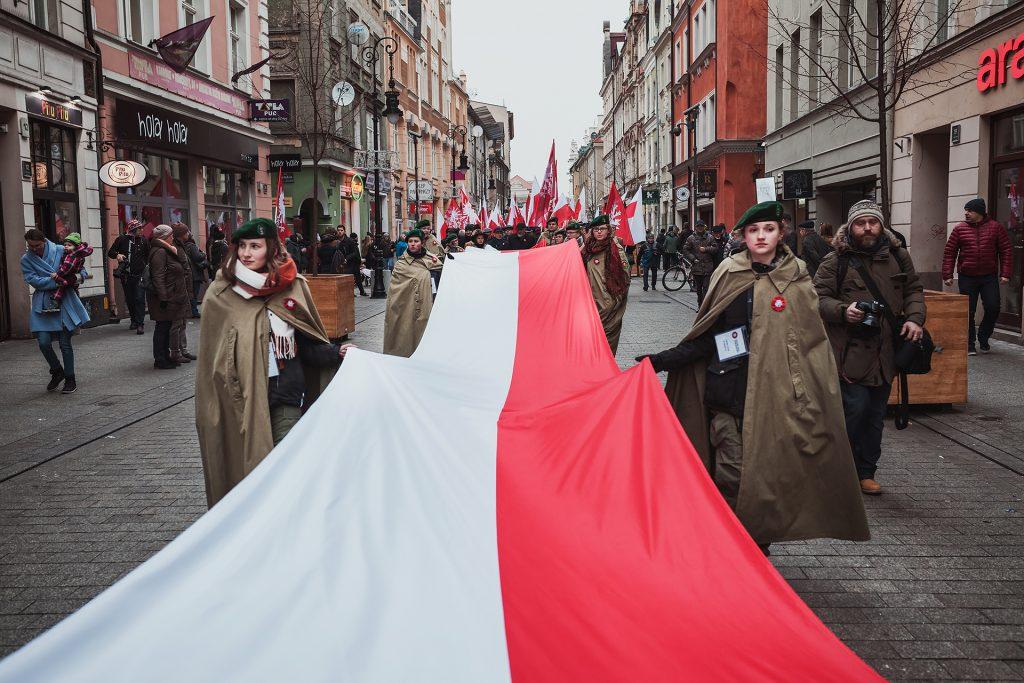 harcerki niosące długą flagę, w tle ludzie z flagami