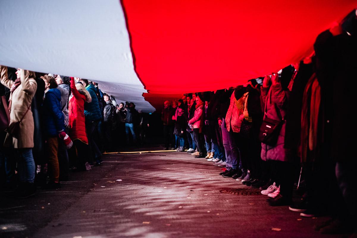 grupa ludzi trzymająca 100-metrową flagę Polski