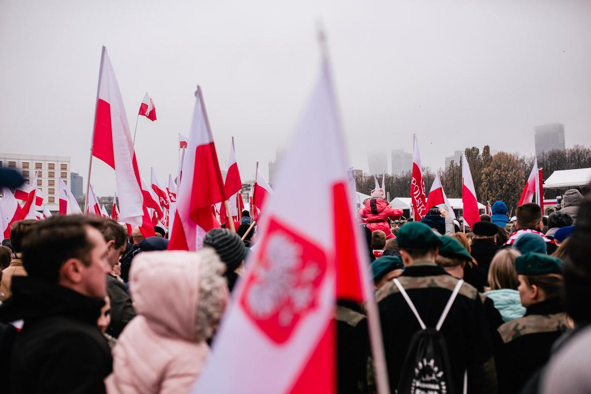tłum ludzi maszerujący z biało-czerwonymi flagami