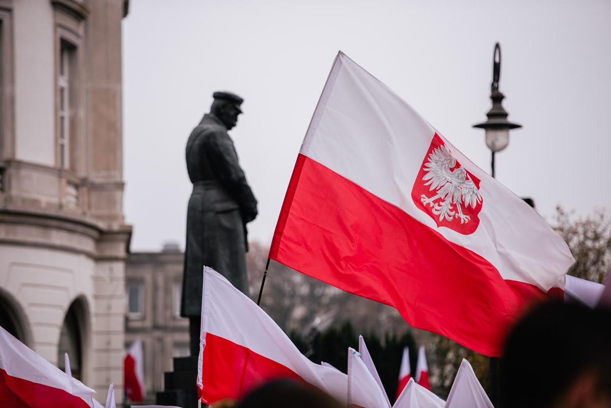 flagi trzymane przez ludzi pod pomnikiem Piłsudskiego