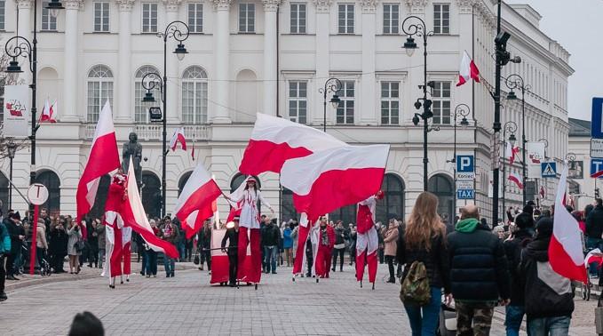 grupa szczudlarzy w biało-czerwonych strojach paraduje po ulicy