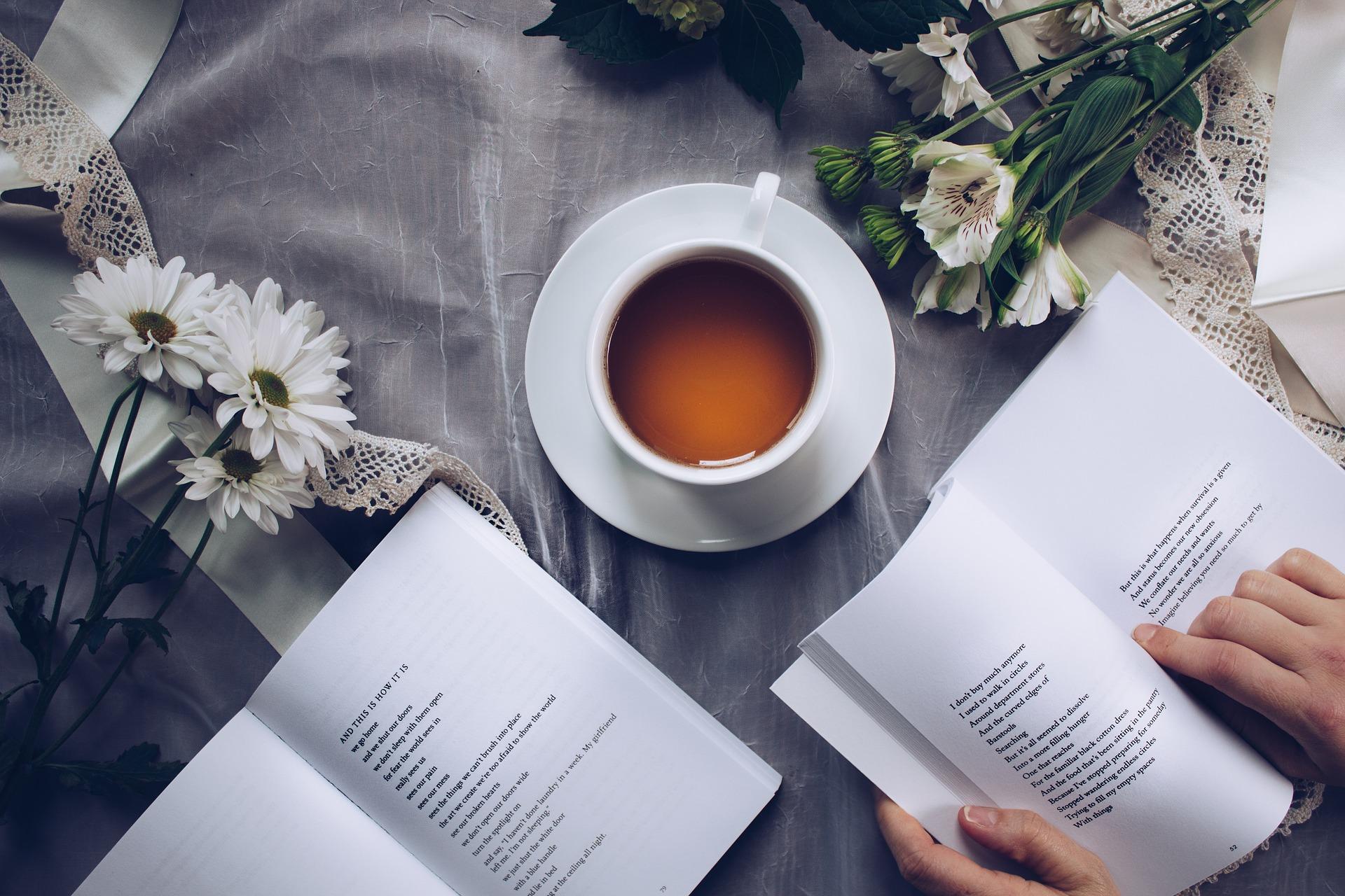 dwa tomiki wierszy na stole przy herbacie