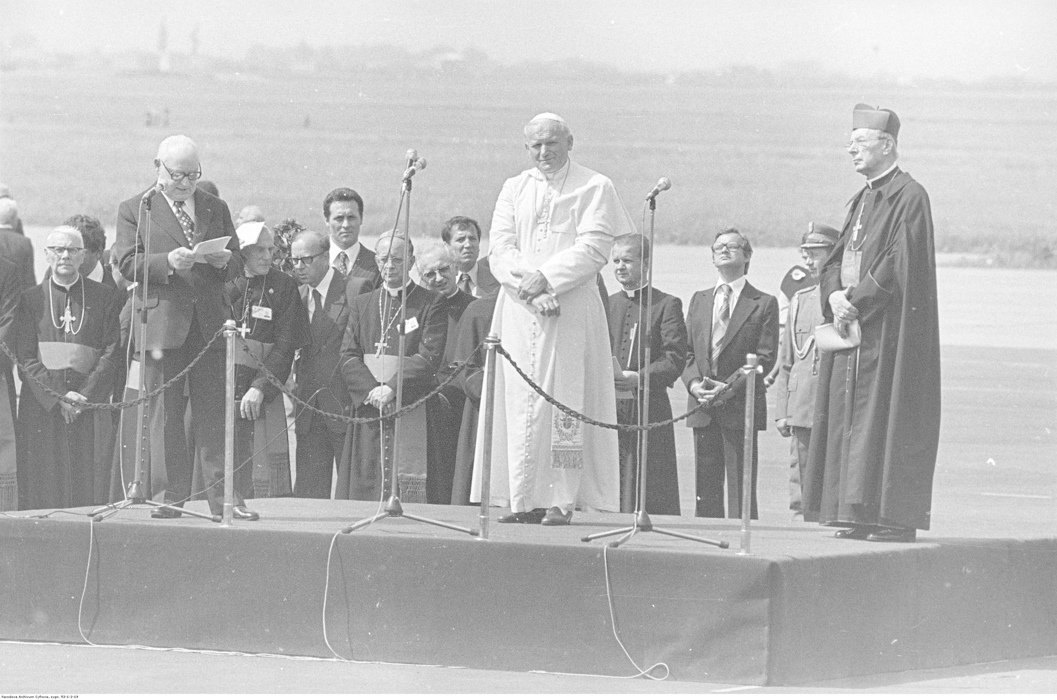 na lotnisku ustwione podium, na nim stoją papież i inny przemawiający mężczyzna, w tle rząd mężczyzn w odświętnych strojach