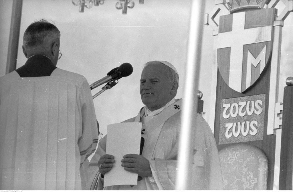 W centrum Jan Paweł II przygotowuje się do homilii. Z lewej widoczny ceremoniarz papieski, ks. prał. Virgilio Noe przygotowujący mikrofon. Z prawej widoczny herb papieża Jana Pawła II jako element tronu papieskiego.