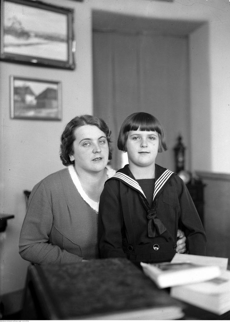 czarno-białe zdjęcie przedstawiające matkę z synem w stroju marynarskim