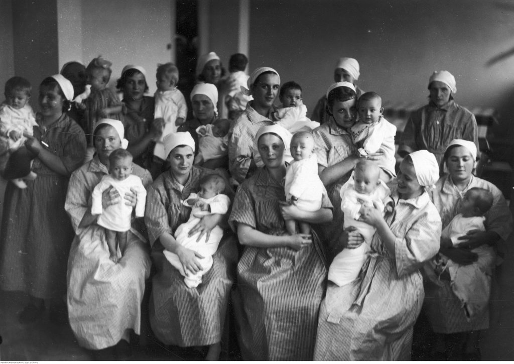 czarno-białe zdjęcie przedstawiające kobiety trzymające na rękach małe dzieci