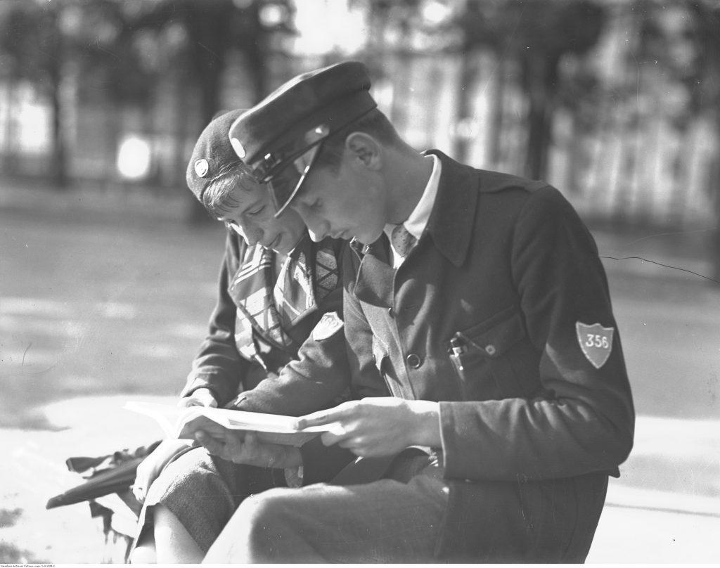 Uczeń i uczennica gimnazjum ubrani w nowe mundurki podczas lektury książki, 1933, fot. NAC