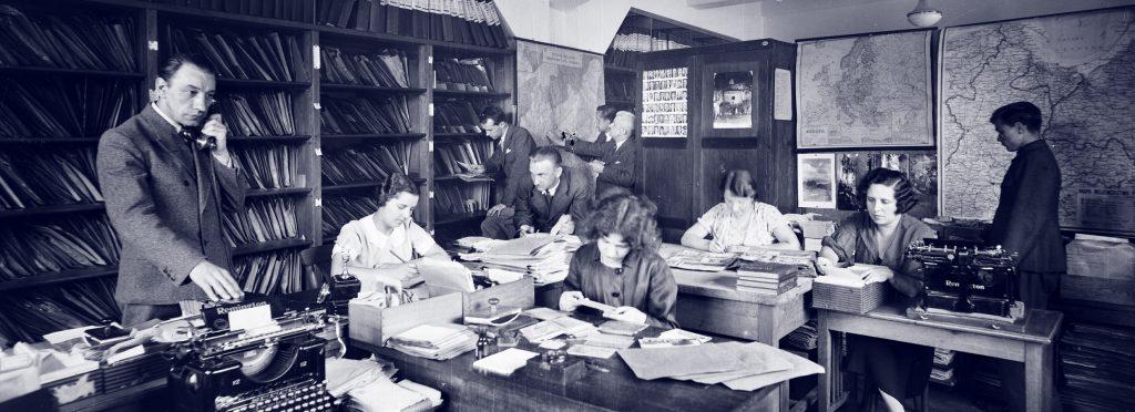 grupa ludzi w pracowni pochylonych nad materiałami archiwalnymi