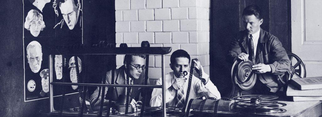 mężczyźni w pracowni przy biurku przeglądający klisze
