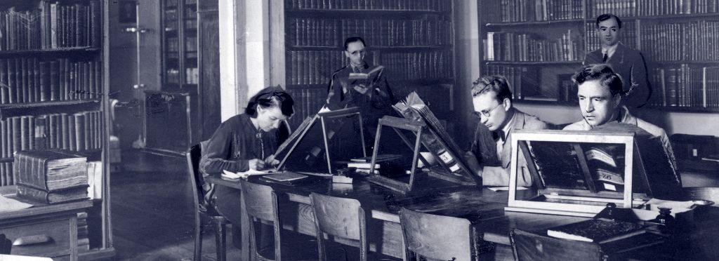 pracownicy w bibliotece przy biurku czytają stare, wielkie księgi