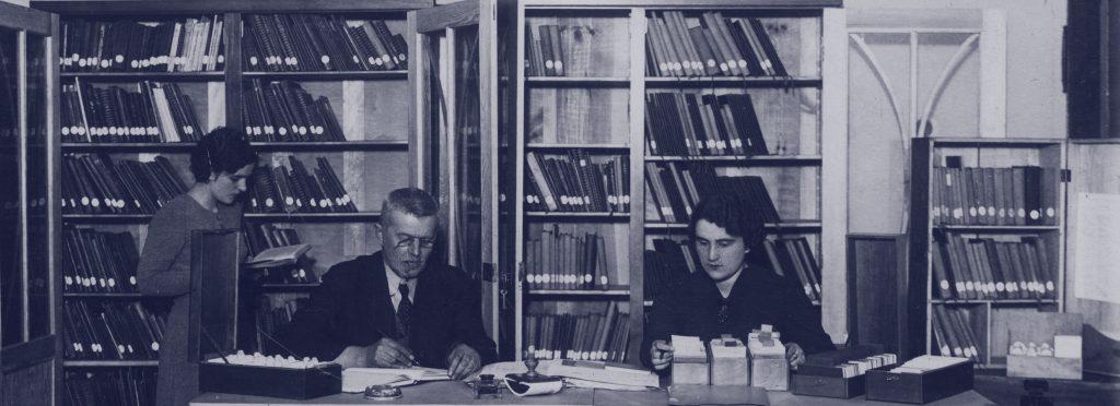pracownicy przy biurku z rozłożonymi archiwaliami
