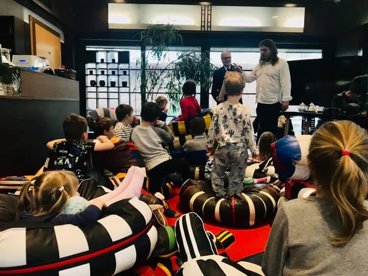 grupa dzieci sziedzi na poduchach i słucha prowadzącego