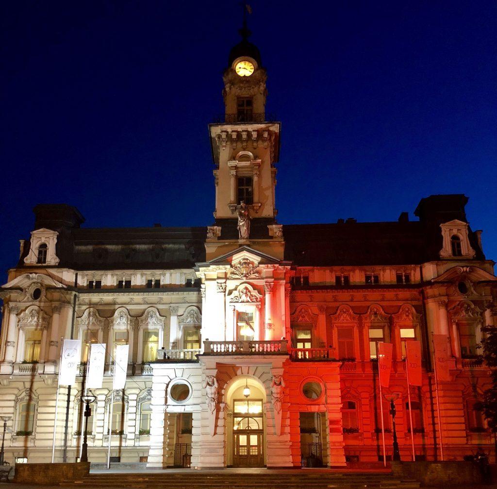 eklektyczny ratusz z wieżą po środku, strona lewa podświetlona jest na biało, prawa na czerwono - w kolorach polskiej flagi