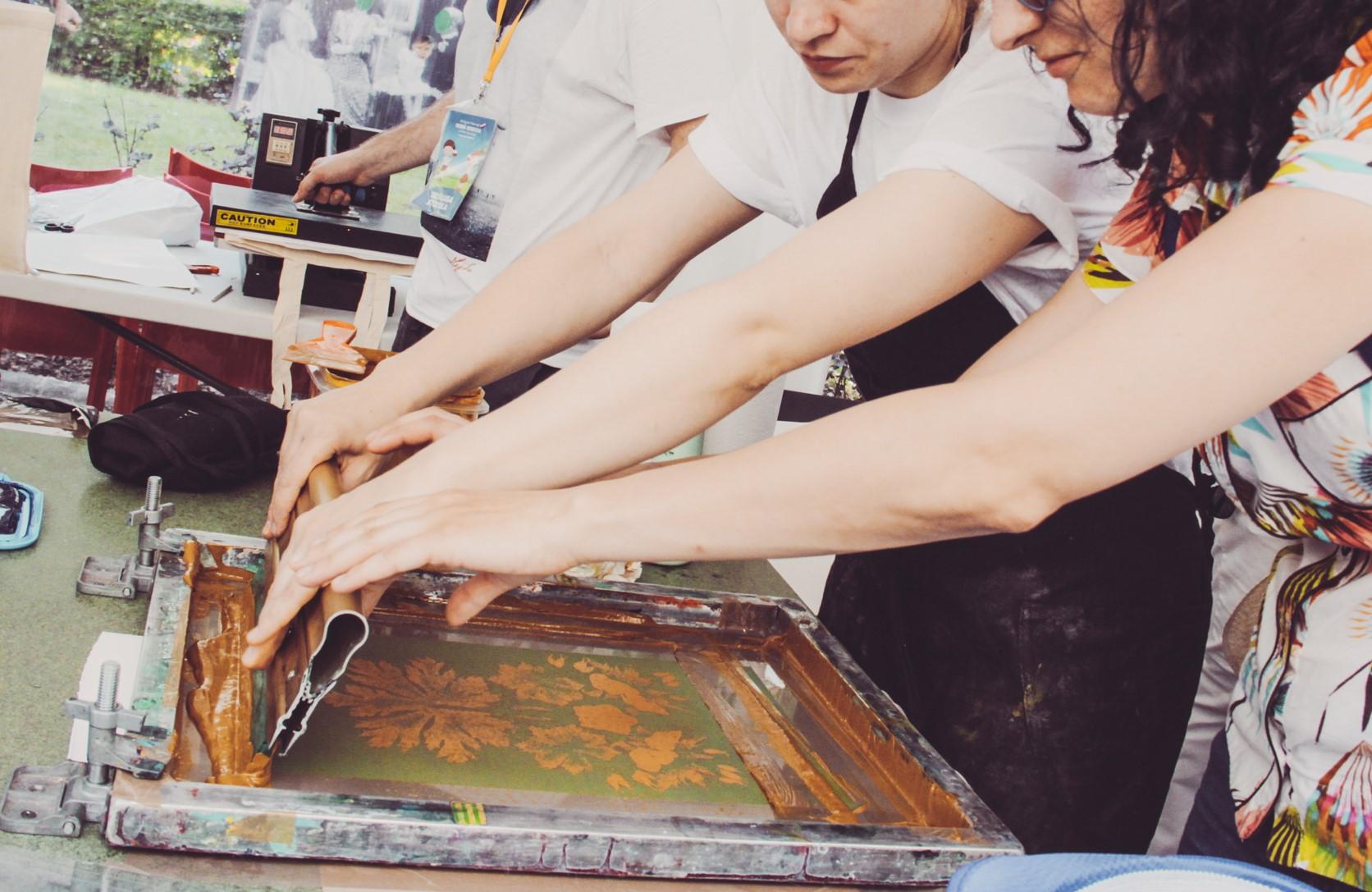 ręce dwóch osób i maszyna do sitodruku w trakcie przenoszenia wzoru