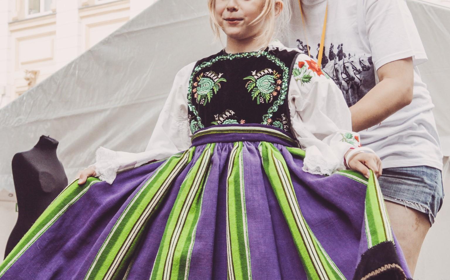 dziewczynka prezentuje przymierzony tradycyjny strój polski
