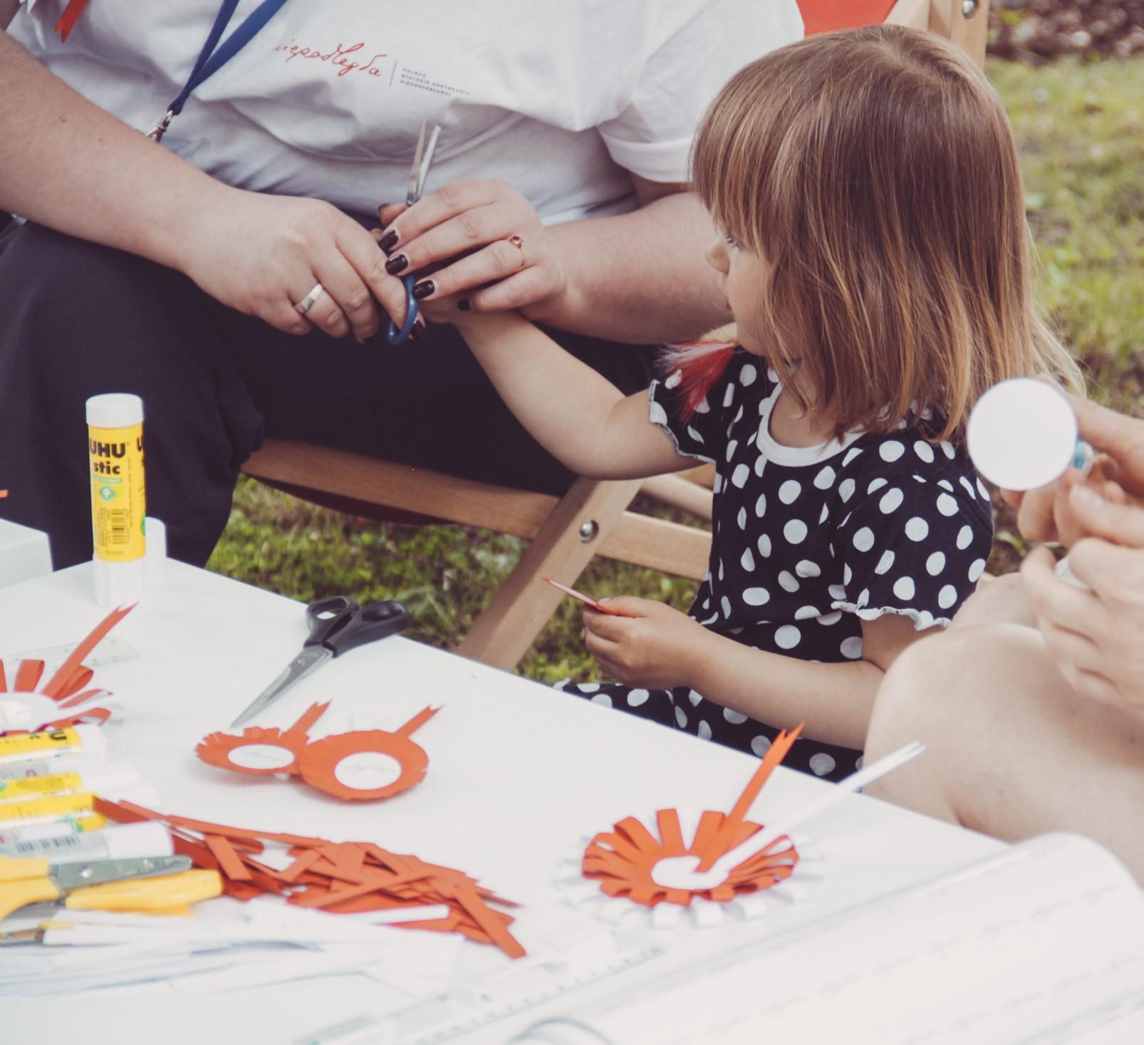 przy stole dziewczynka lepiąca kotyliony z przygotowanych elementów