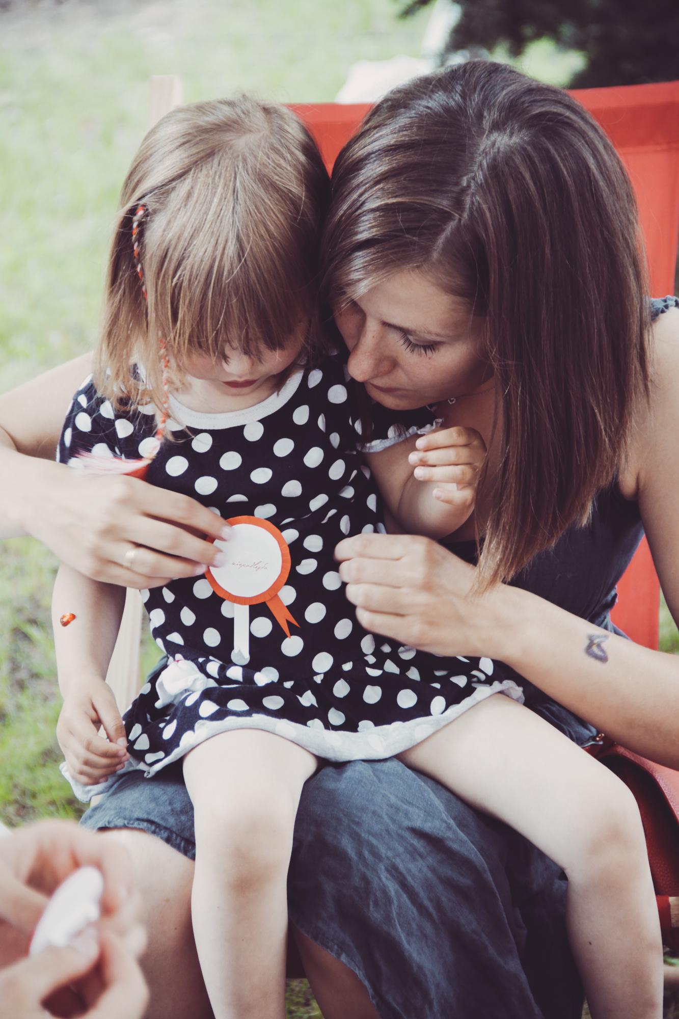 dziewczynce trzymanej na kolanach mama przypina ręcznie robiony kotylion