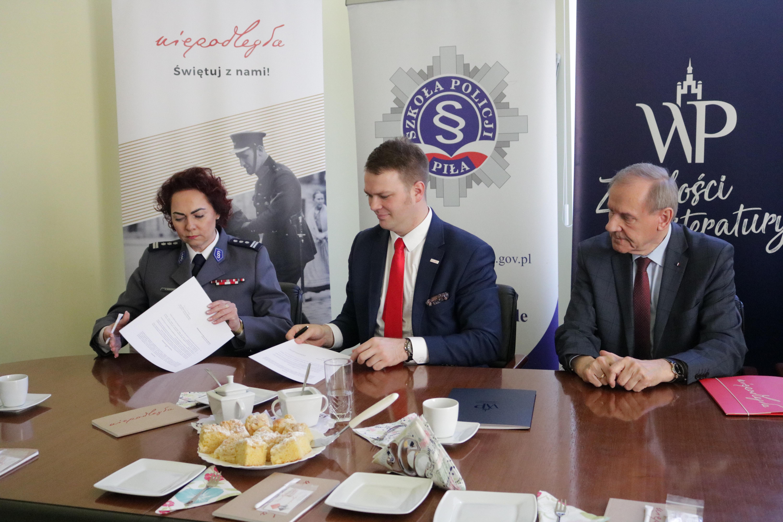 zdjęcie trzech siedzących osób, podpisujących dokumenty
