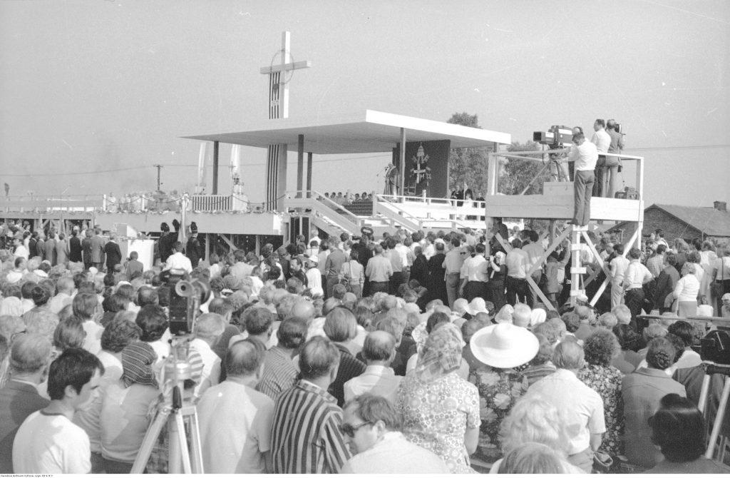 W centrum widoczny ołtarz, przy tronie papieskim widoczny Jan Paweł II, z prawej - stanowiska operatorów kamer, cała przestrzeń jest wypełniona ludźmi przybyłymi na spotkanie.
