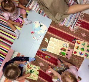 małe dzieci siedzące na dywanikach z rozłożonymi zabawkami edukacyjnymi