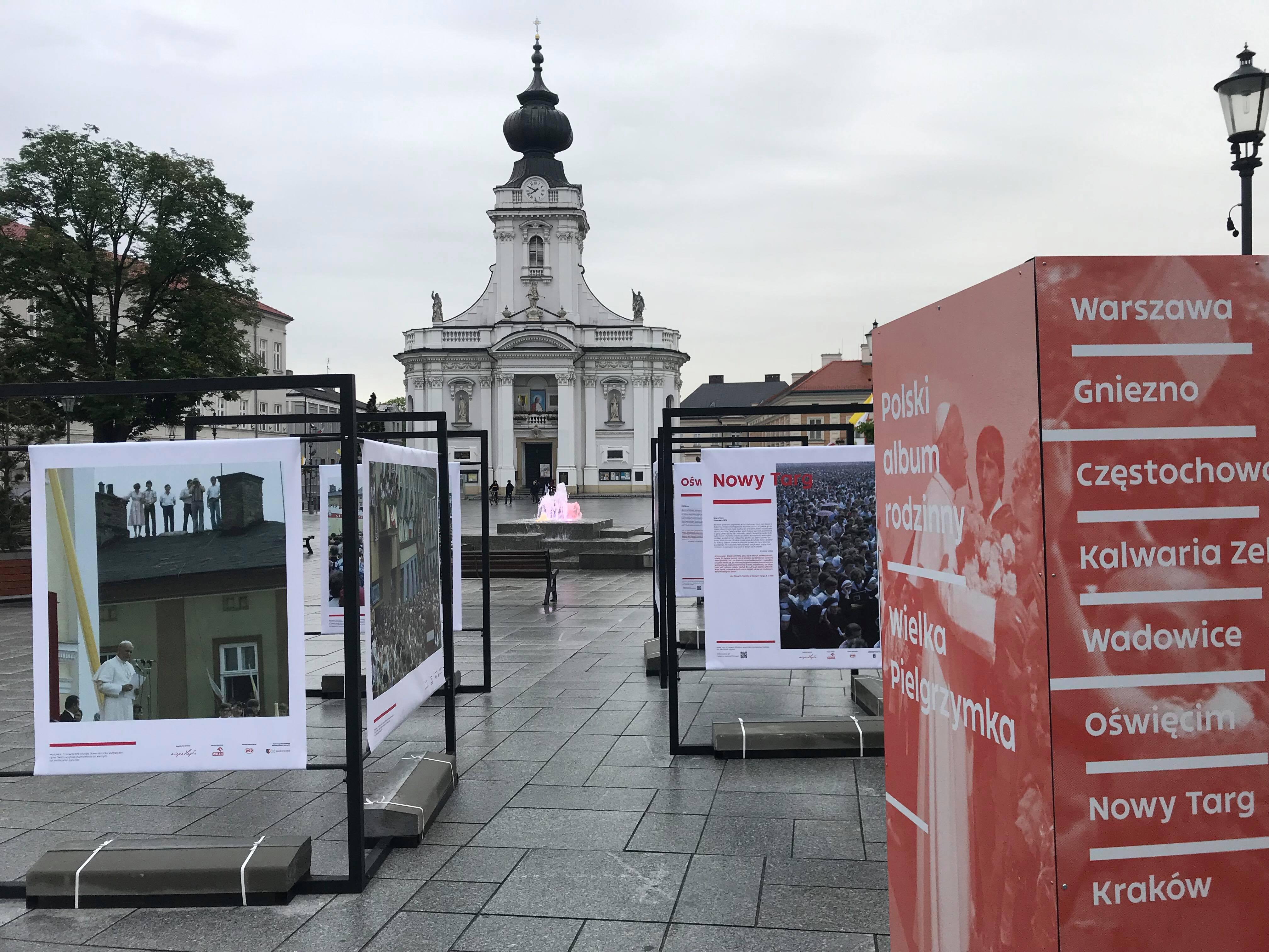 wystawa planszowa rozstawionka na rynku w Wadowicach, w tle Bazylika Mniejsza Ofiarowania Najświętszej Maryi Panny
