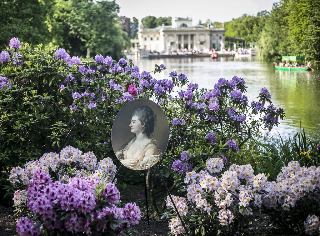portret kobiety z XVIII wieku ukryty w rabatce wśród kwiatów - a tle Pałac na Wodzie