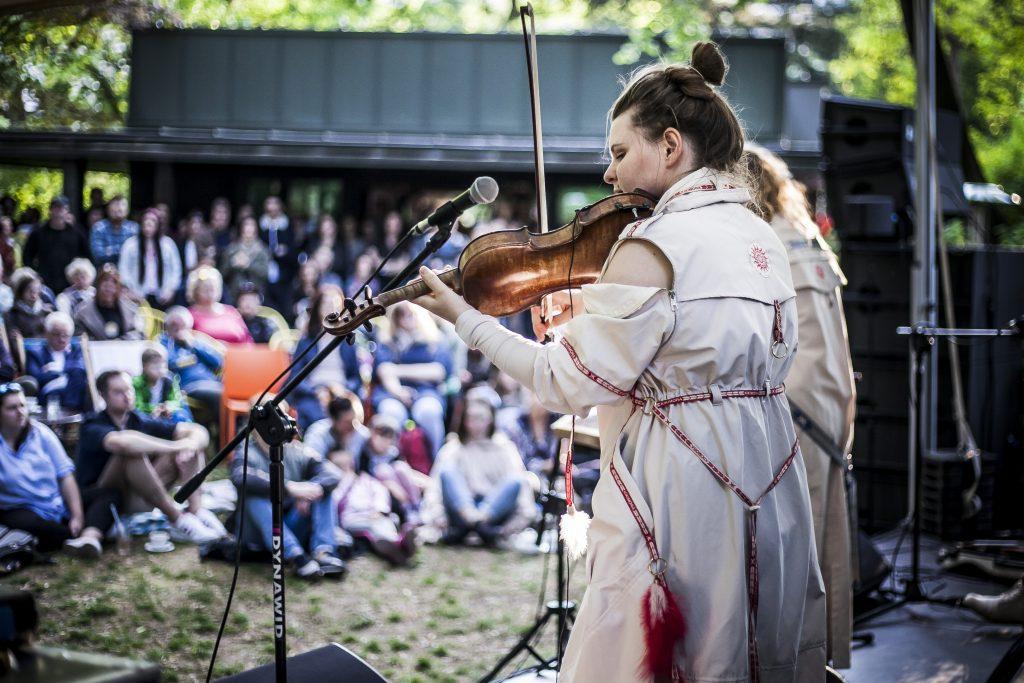 na pierwszy planie dwie artystki grające na skrzypcach, w te publiczność