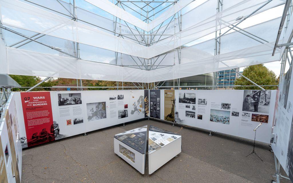 """na dole wystawa złożona z plansz i fotografii, na górze konstrukcja charakterystycznego pawilonu """"po wielkiej wojnie"""""""