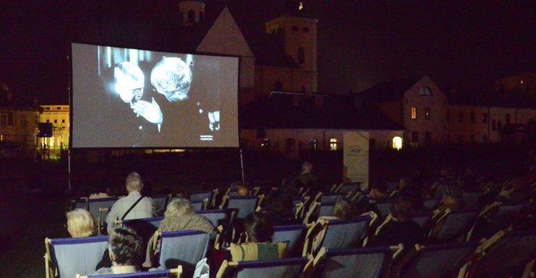fotografia przedstawiająca widzów na leżakach oglądających projekcję filmu w kinie plenerowym