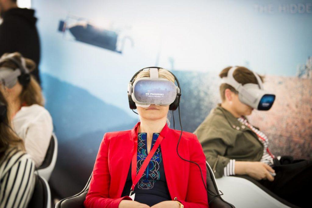 """Zdjęcie promocyjne Wirtualnego Teatru """"Niepodległa"""" - kilka osób siedzących w goglach do VR z napisem MS Piłsudski"""